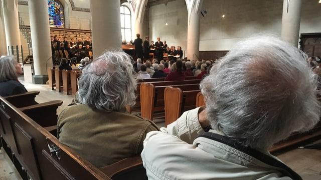Männerköpfe mit grauen Haaren an einem Konzert in der Kirche.