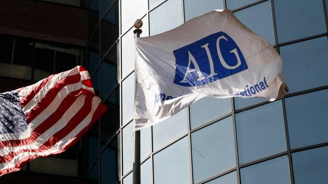 US-Flagge und AIG-Konzernflagge vor der Glasfront eines Hochhauses.