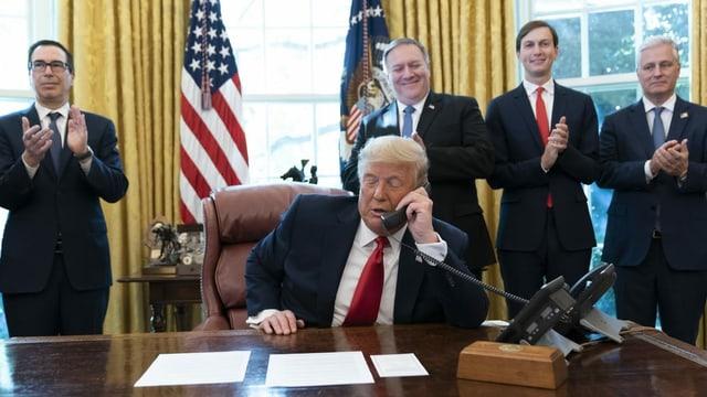 Trump am Telefon. Dahinter stehen Männer, die applaudieren.