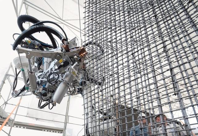 Roboter arbeitet an einer Stahlbetonwand.