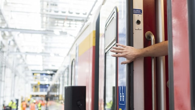 Ina persuna tegna avert ina porta d'in vagun da tren.