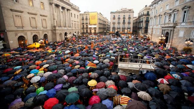 Tausende Menschen stehen unter bunten Regenschirmen auf einem Platz