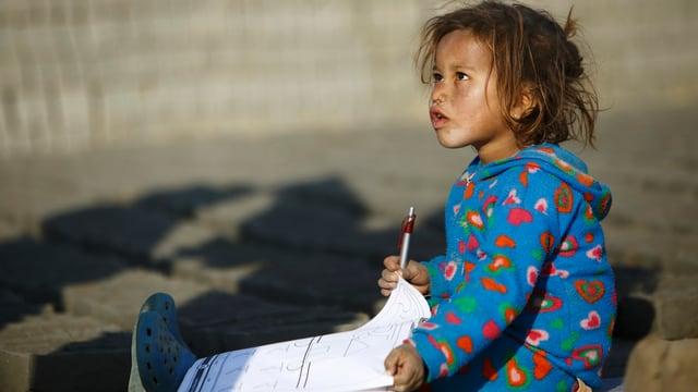 Kleinkind mit Papier am Boden sitzend.