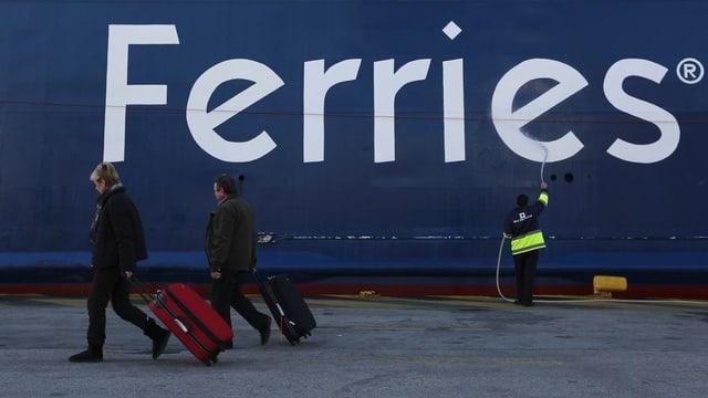 Passagiere vor einer Fähre im Hafen.