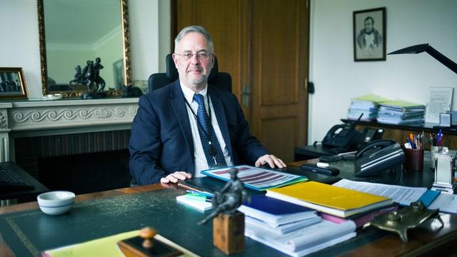 Ein Mann mit grau meliertem Haar sitzt an seinem Schreibtisch.