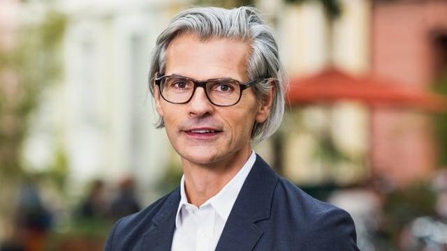 Stefan Charles trägt eine Brille und einen blauen Blazer.