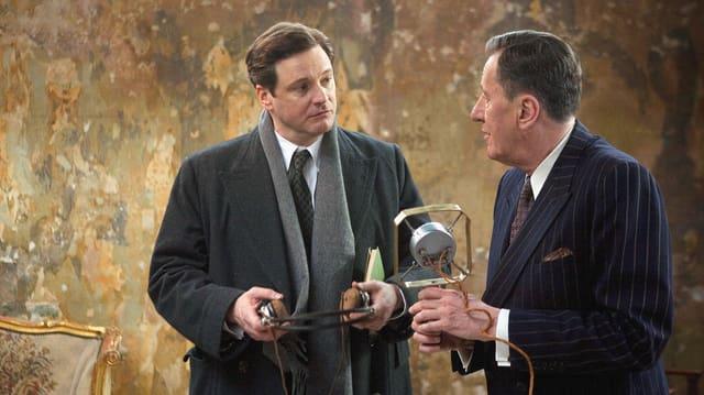 Zwei Männer. Einer hält ein altmodisches Mikrofon in der Hand.