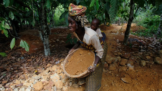 Eine Frau mit Kind trägt Sand, der auf Spuren von Gold untersucht werden soll.