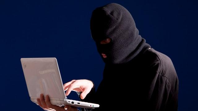 Maskierter Mann mit Laptop