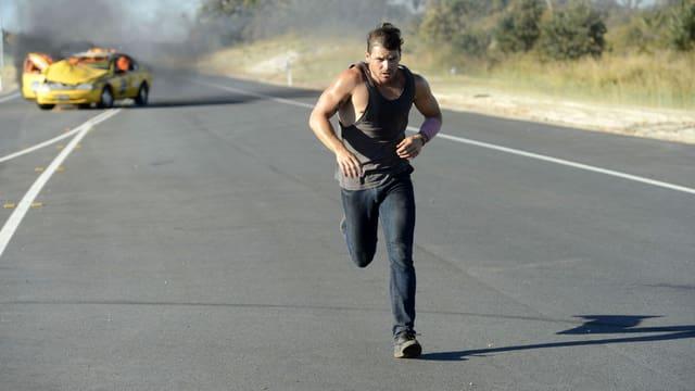 Ein Mann rennt weg von einem brennenden Auto.
