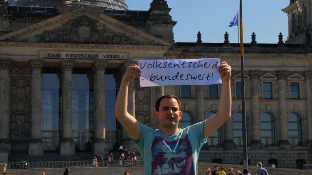 Mann vor deutschem Bundestag mit Schrift: Volksentscheid - bundesweit.
