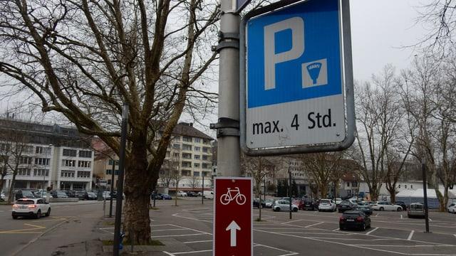 Parkplatz. Parktafel im Vordergrund. Hinten ein wenig besetzter Parkplatz.