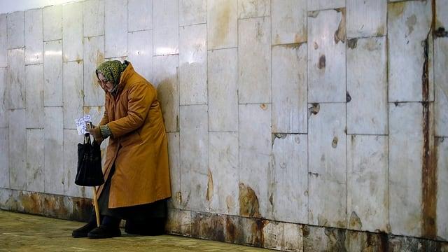 Eine alte Frau lehnt an einer Mauer in einer Unterführung.