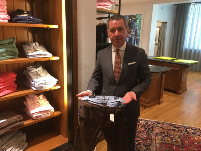 Franco Savastano zeigt eine Hose neben einem Gestell mit Herrenkleidern.