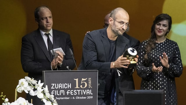 Ein Mann hält den soeben erhaltenen Preis-Pokal vor das Publikum.