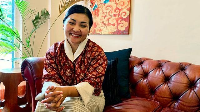 Eine Frau sitzt lächelnd auf einem Sofa