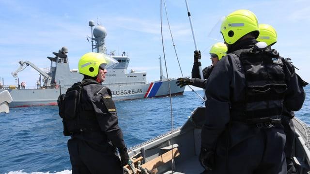 Isländische Frontex-Einsatzkräfte mit gelben Helmen auf einem Boot.