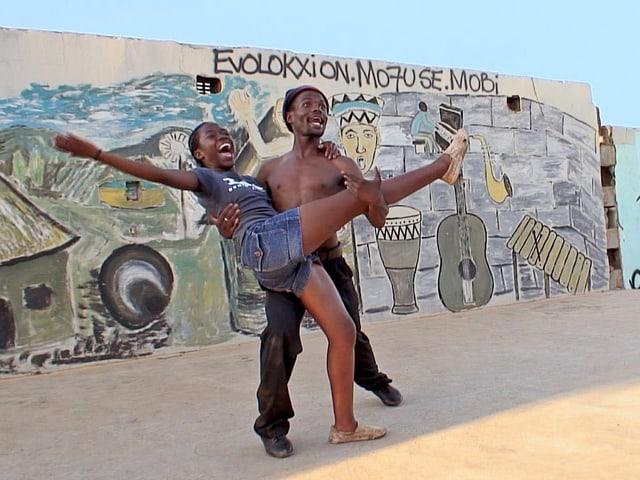Zwei junge Menschen tanzen vor einer bemalten Wand.