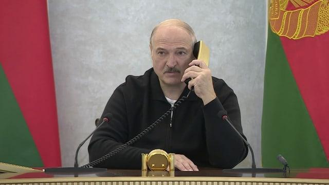 Lukaschenko telefoniert mit einem goldenen Telefon und blickt nachdenklich in die Ferne.