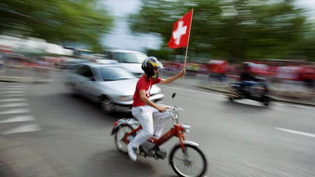 Ein Schweizer Fussballfan fährt auf seinem Mofa durch die Strassen und hält dabei eine Schweizer Fahne in die Höhe.
