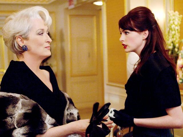 Eine Frau mit schwarzem Kleid und Pelzmantel zieht ihre Handschuhe aus. Daneben steht eine jüngere Frau, sie sprechen miteinander.