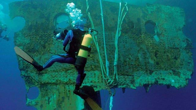 Ein Taucher neben einem Schiffswrack unter Wasser.