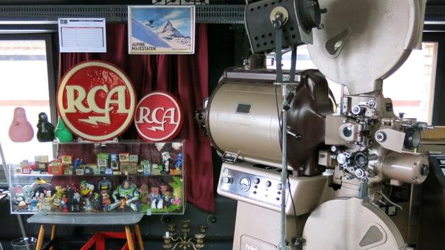 Ein Projektor steht neben einer Vitrine mit Filmfiguren aus Plastik.