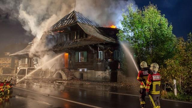 Feuerwehrleute spritzen Wassen in ein brennendes Haus