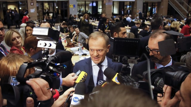 Donald Tusk circumdà da schurnalists cun microfons e cameras.