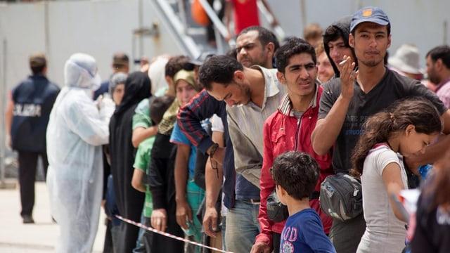 Flüchtlinge in einer Schlange vor einem italienischen Militärschiff