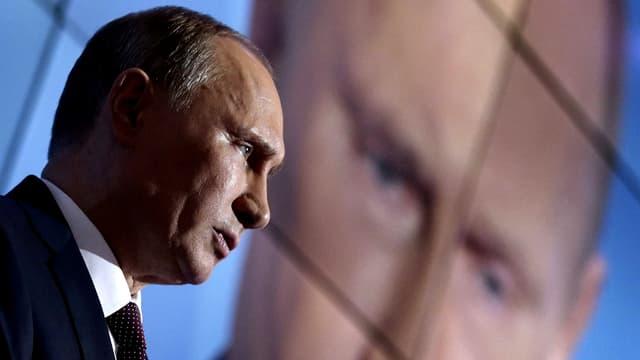 Putin vor einer Leinwand, die gross sein Gesicht zeigt.