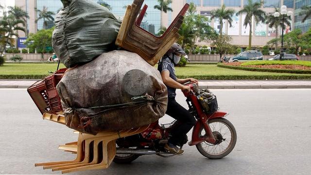 Person auf Mofa mit viel Gepäck.
