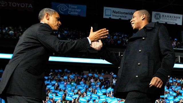 Obama und Jay-Z reichen sich auf der Bühne die Hand.