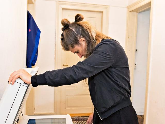 Frau hält Deckel eines Druckers auf.
