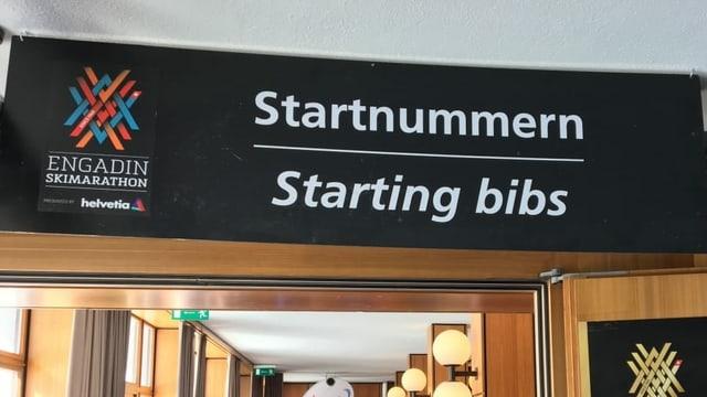 "Da vesair sin il purtret è in grond placat cun scrit si ""Startnummern / Starting bibs"" a la partenza dal Maraton da skis engiadinais."