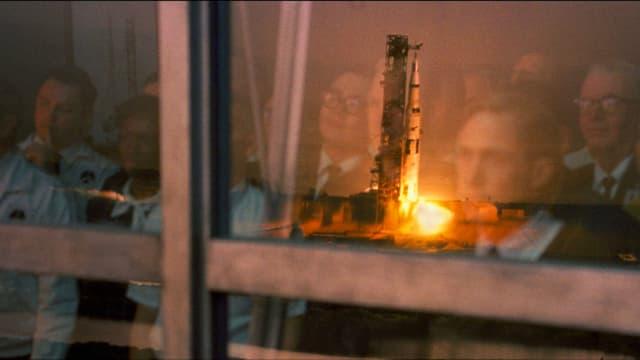 Rakete startet. Menschen spiegeln sich im Fenster, durch welches sie den Start beobachten.