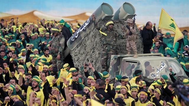 Männer in gelben Hisbollah-Shirts, auf einem Fahrzeut zwei Raketenwerfer.