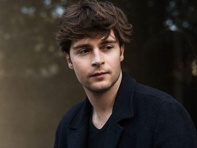 Junger Mann, kurze braune Haare, blaues Jacket schaut in die Ferne