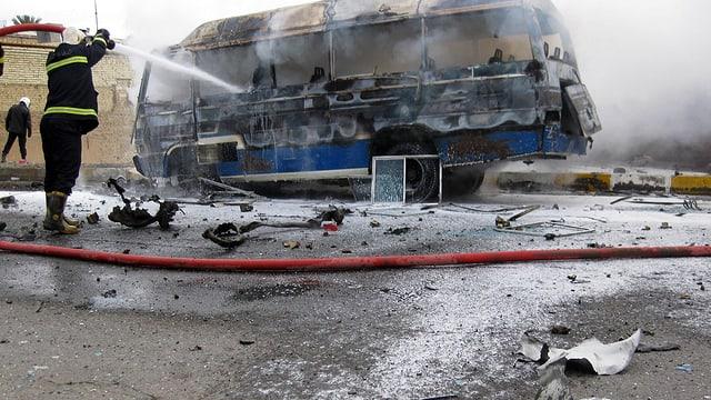 Feuerwehrmann löscht brennenden Bus.