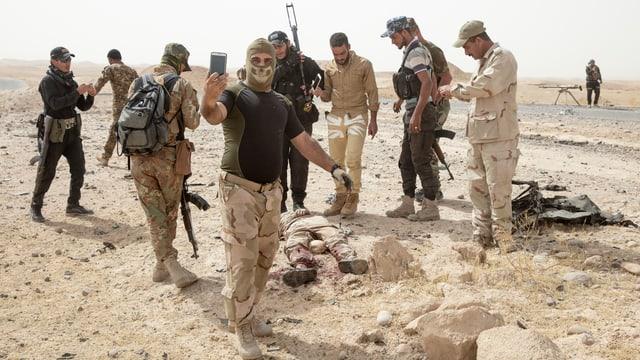 Ein Bild von Soldaten, die um eine Leiche herum stehen.