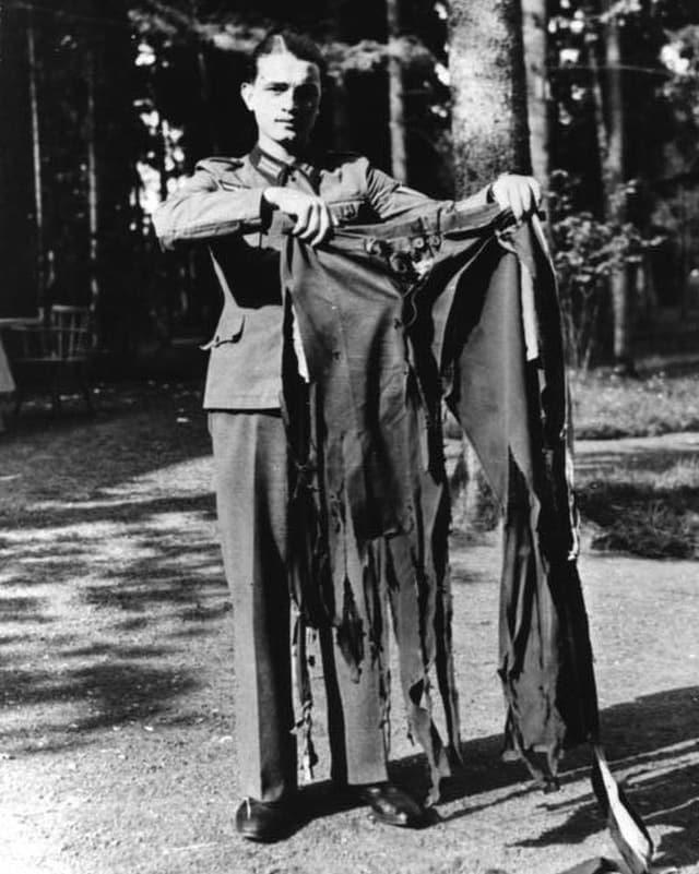 Ein Soldat auf einer Waldstrasse hält eine zerfetzte Hose in die Kamera.