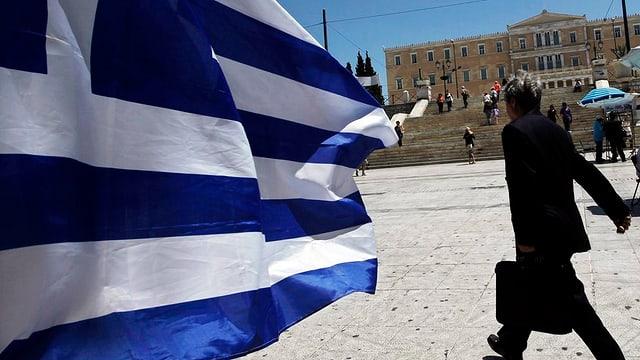 Mann mit Aktentasche neben griechischer Fahne.