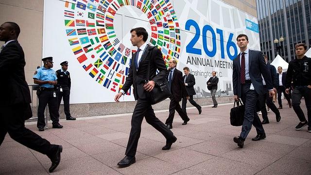 Businessmänner gehen an einem 2016-Schild vorbei.