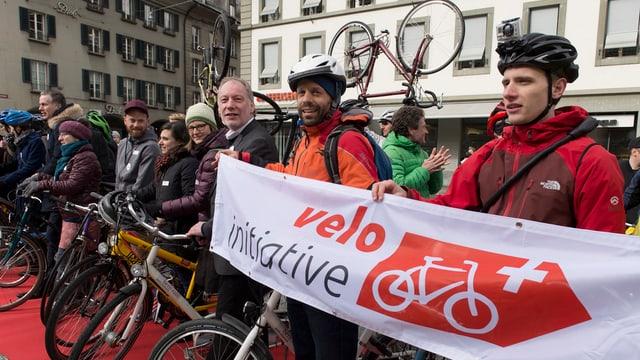 velocipedists en colona che tegnan in placat cun si iniziativa da velo