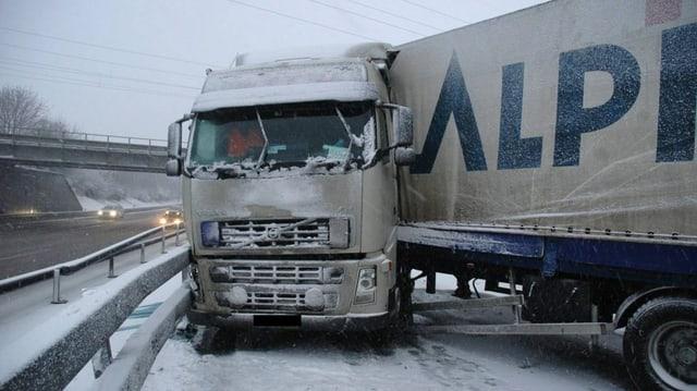 Ein Lastwagen kommt bei Schnee von der Fahrban ab