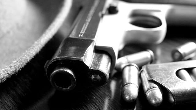Hut liegt neben einem Revolver mit Munition.