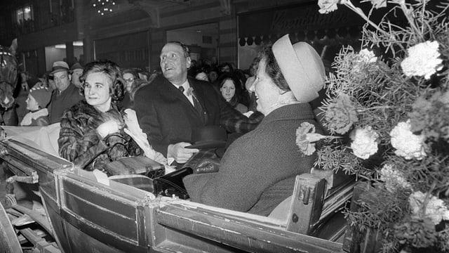 Mann und zwei Frauen in Kutsche.