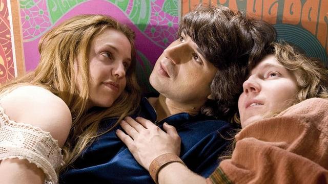Der junge Elliot liegt in der Mitte eines Paars.