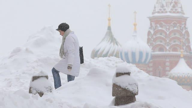 Purtret d'ina dunna che passa sur la plazza dal Kreml ora.
