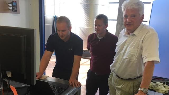 Drei Männer stehen um einen Computer herum.